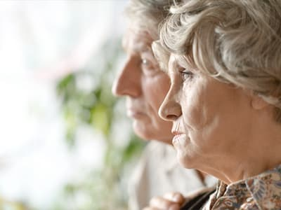sad elderly couple looking out window