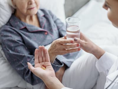 nurse gives elderly patient pills with water