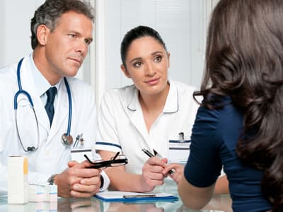 Doctors talking with hispanic patient about available rehab options