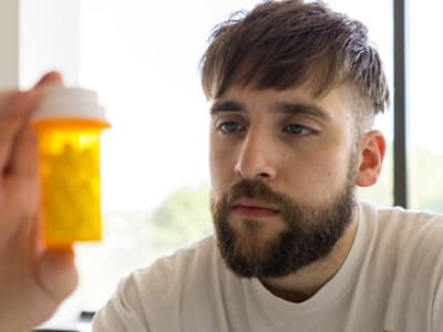 male blue collar worker staring at pill bottle in hand