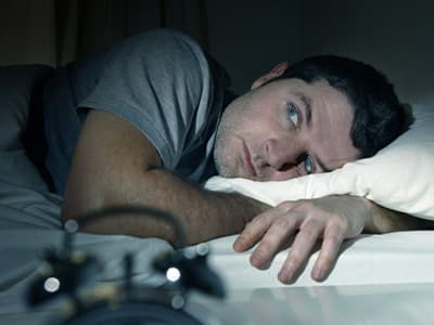 Man portraying a veteran trying to sleep suffering from depression