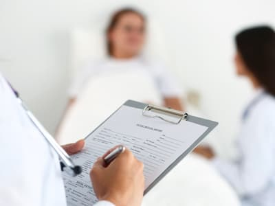doctor writes on clipboard with patient in background