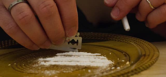 close-up of person cutting lines of cocaine