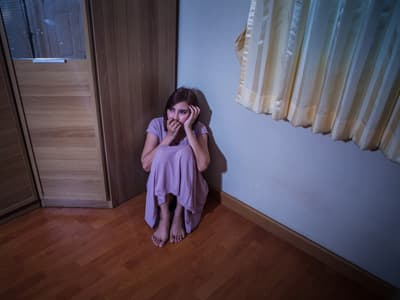 Young woman sitting in corner portraying a person experiencing a bad trip on Psilocybin mushrooms