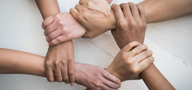 diverse hands holding onto eachother in support