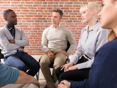 Diverse community of individuals participating in group therapy for addiction treatment