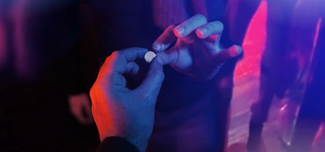 Close-up of hand passing club drug pill to another