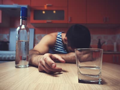 Man suffering from alcoholism with head down on table reaching for glass of alcohol in front of him