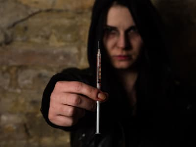 Woman standing in dark room holding syringe with heroin inside portraying a heroin addict