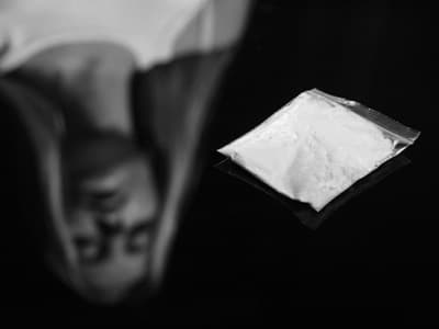 reflection of woman standing over packet of meth portraying a meth addict in the united states