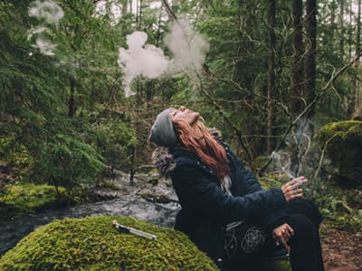 blonde woman sitting in woods blowing marijuana smoke into the air