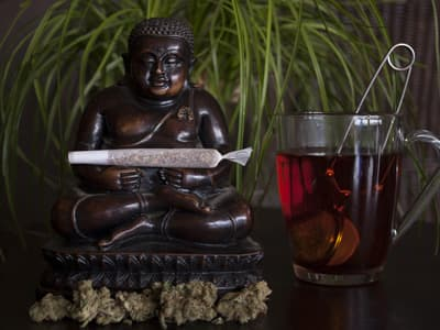 small buddha statue holding joint sitting next to marijuana tea