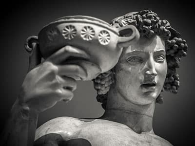 greek statue holding up cup of wine