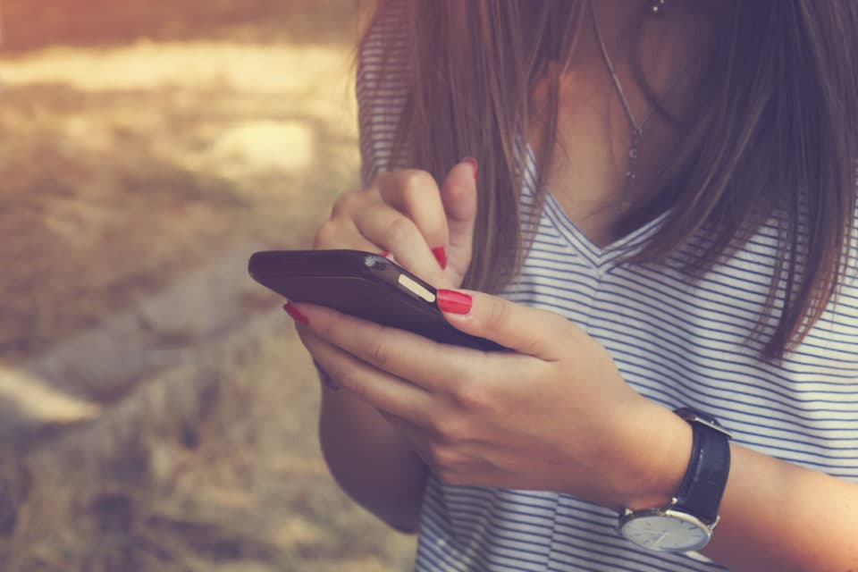 Young woman using cellphone outdoors.