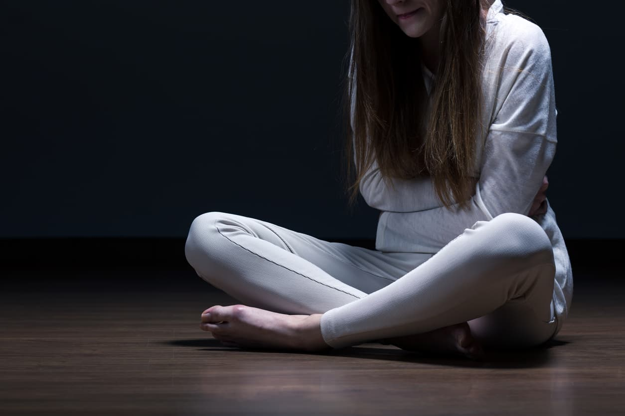 Picture of despair female with mental problem sitting on floor