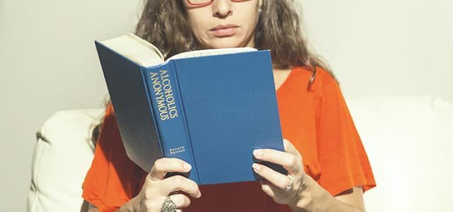Woman reading Alcoholics Anonymous Big Book AA Promises section