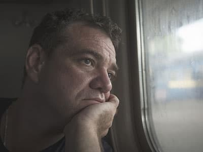depressed man looking out window