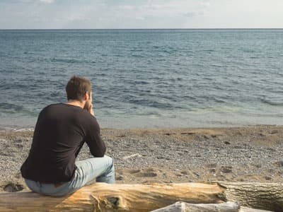 Man sitting and staring out at the ocean