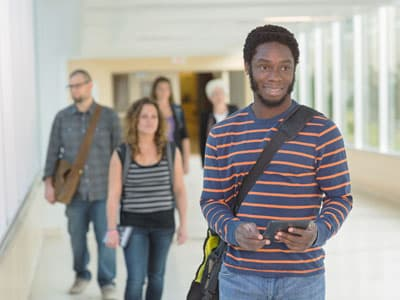 Young man walking through college hallway
