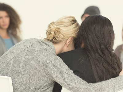 Women hugging in support group for clonazepam addiction