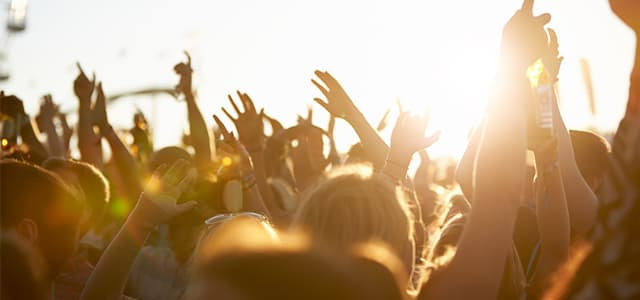 People with hands up at festival