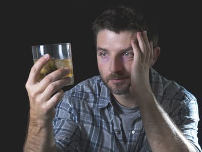 Man going through withdrawal staring at alcohol