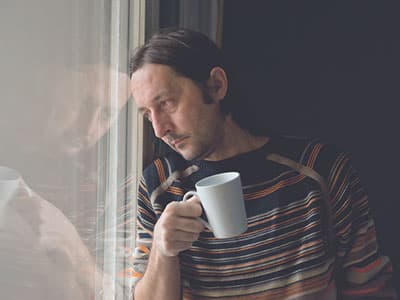 Depressed man staring out window