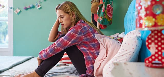 recovery-shutter283541576-teenage-girl-sitting-on-bed