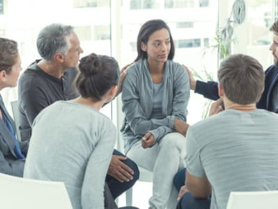Woman in group therapy for addiction treatment
