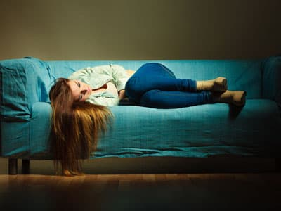 Girl in fetal position on couch