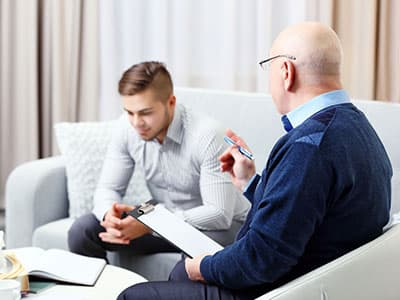Therapist talking to young man about barbiturate abuse