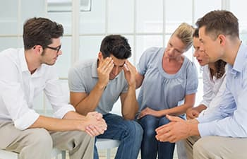 AA members comforting man at 12-step meeting
