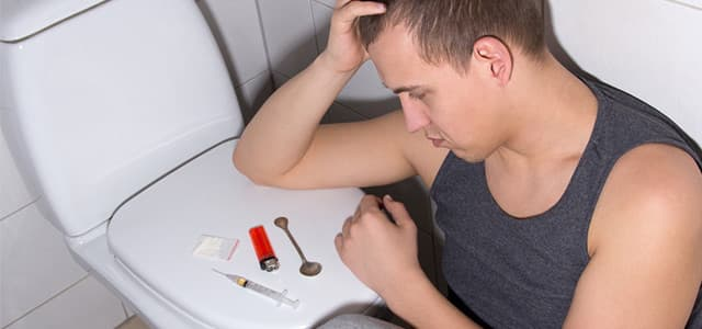 young man struggling with heroin addiction in bathroom